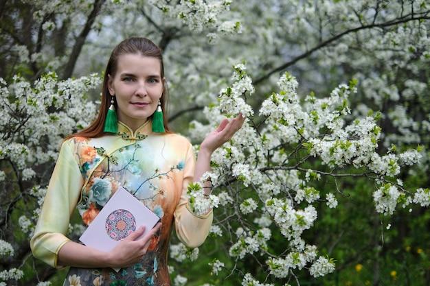 Hermosa chica en estilo chino en flores de cerezo