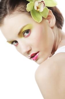 Hermosa chica con estilo con orquídeas phalaenopsis en el cabello