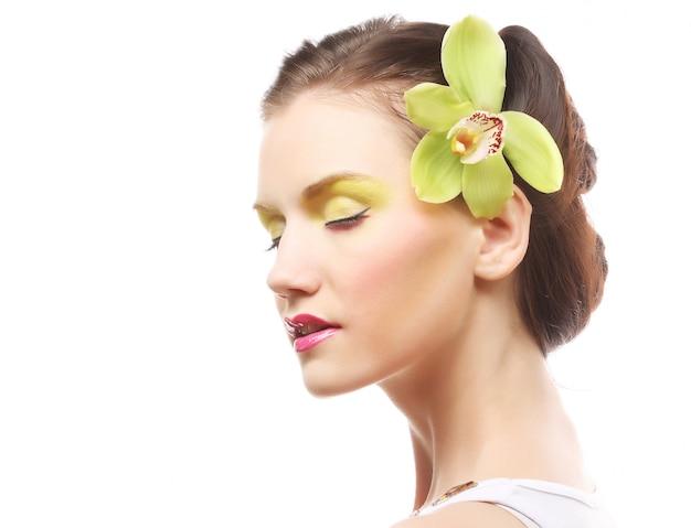 Hermosa chica con estilo con orquídeas phalaenopsis en el cabello.