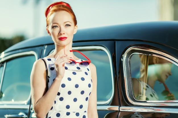 Hermosa chica en estilo retro y un auto clásico