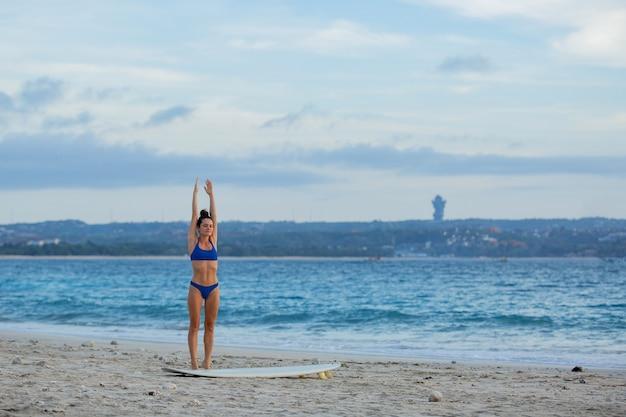 Hermosa chica estirándose en la playa con una tabla de surf.