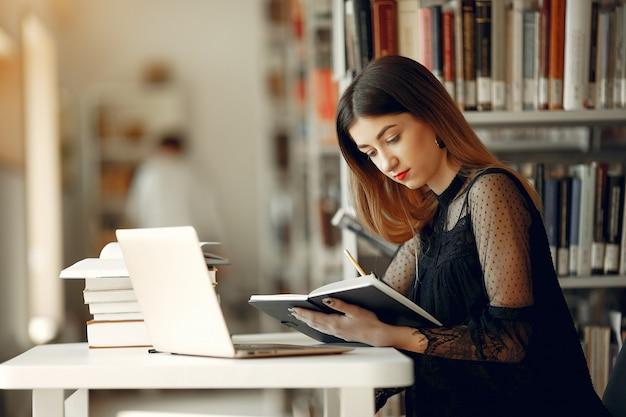 Hermosa chica estudia en la biblioteca