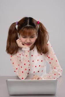 Hermosa chica estudiante asiática mira la computadora portátil mientras hace la tarea haciendo videollamada