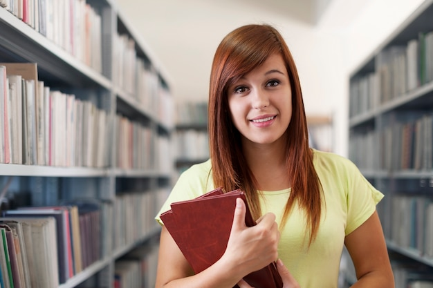 Hermosa chica estudiante sosteniendo libros en la biblioteca