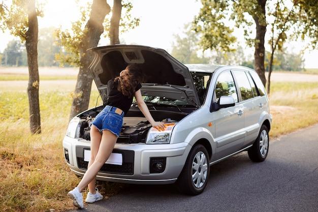 Hermosa chica estudiante vistiendo mini shorts y camiseta negra apoyada en el capó abierto de un automóvil moderno averiado