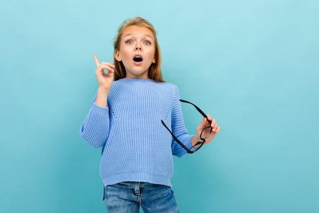 Hermosa chica europea con gafas en la mano en la pared azul claro