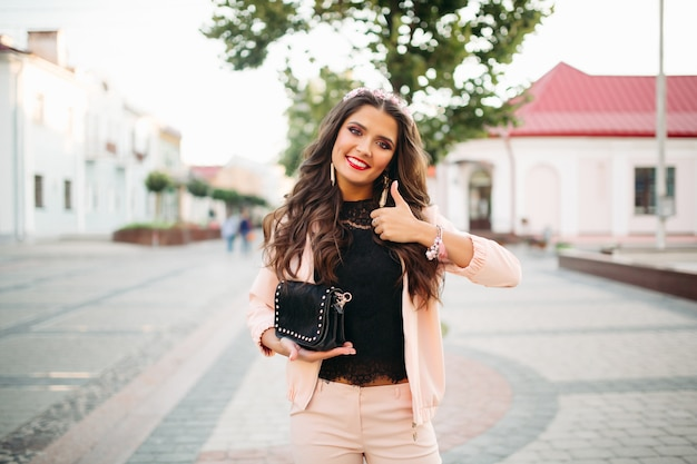 Hermosa chica feliz con el bolso negro de moda que muestra el pulgar hacia arriba.
