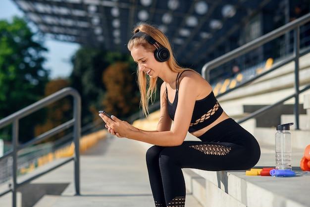 Una hermosa chica de fitness en ropa deportiva gris usa un teléfono inteligente y escucha música en el estadio después del entrenamiento.