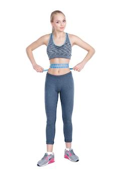 Hermosa chica fitness en ropa deportiva mide su cintura con cinta métrica sobre fondo blanco.