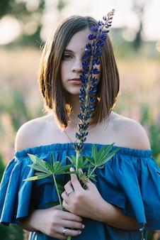 Hermosa chica con una flor de lupino en sus manos en un campo al atardecer cubre su rostro.