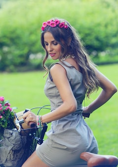 Hermosa chica con flores en bicicleta