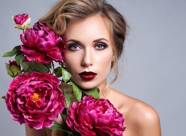 Hermosa chica con flores de primavera.