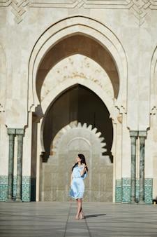 Hermosa chica en el fondo de la mezquita de hassan ii en casablanca marruecos