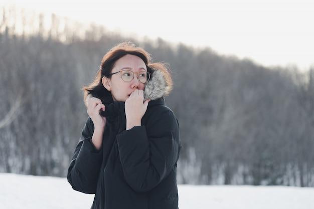 Hermosa chica, con frio, con ropa de invierno entre los pinos.