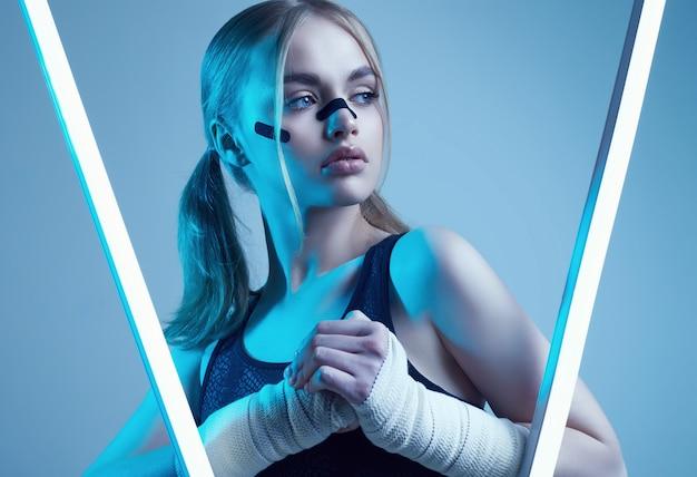 Hermosa chica fuerte con cabello rubio, mirada segura, puños en vendas protectoras de boxeo