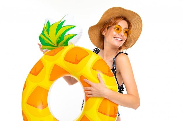 Hermosa chica con gafas y un sombrero de paja con un círculo de natación en forma de piña en una pared blanca