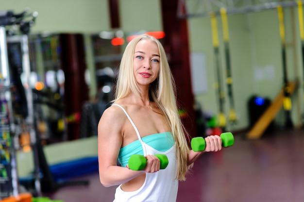 Hermosa chica en el gimnasio, se dedica con pesas