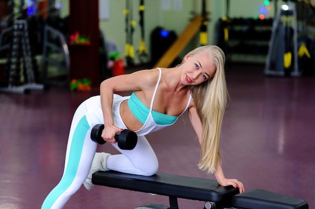 Hermosa chica en el gimnasio, se dedica a pesas