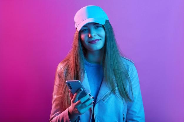 Hermosa chica con gorra de canasta y chaqueta de cuero, sosteniendo un moderno teléfono inteligente en las manos, mirando sonriendo directamente a la cámara