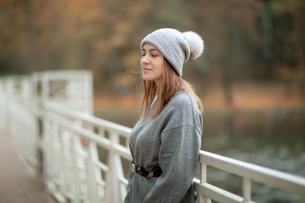 Hermosa chica con gorro de lana hecho a mano de punto gris con un pompón y un suéter disfruta de la naturaleza junto a un puente