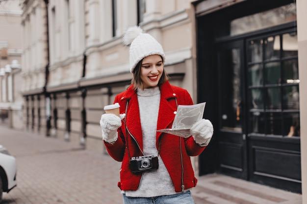 Hermosa chica con gorro de punto y guantes examina el mapa de lugares de interés. mujer en abrigo rojo con vidrio de cartón y cámara retro.