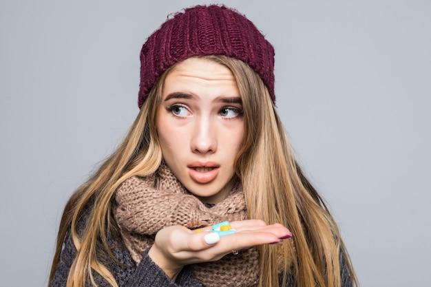 Hermosa chica con gripe o resfriado tiene una gran cantidad de medicamentos para tomar para estar saludable en gris