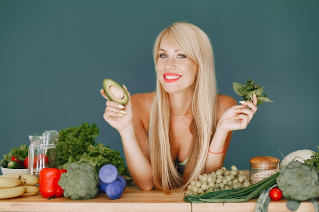 Hermosa chica hace una ensalada. rubia deportiva en una cocina. mujer con aguacate.