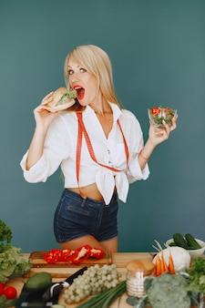 Hermosa chica hace una ensalada. rubia deportiva en una cocina. la mujer elige entre hamburguesa y ensalada.