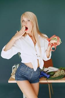 Hermosa chica hace una ensalada. rubia deportiva en una cocina. la mujer elige entre hamburguesa y pimienta.