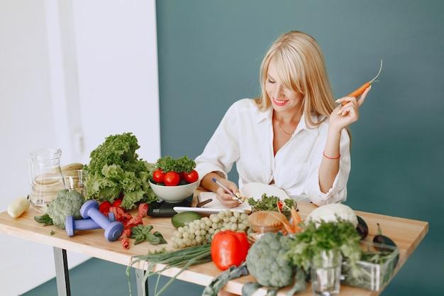 Hermosa chica hace una ensalada. rubia deportiva en una cocina. receta de escritura de mujer en el cuaderno.