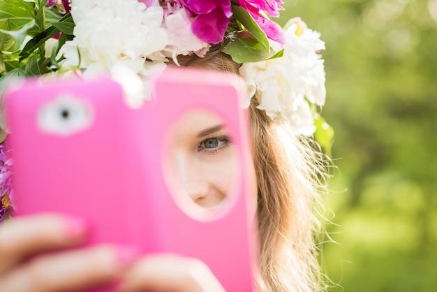 Hermosa chica hace una selfie. marco de la caja del teléfono rosa