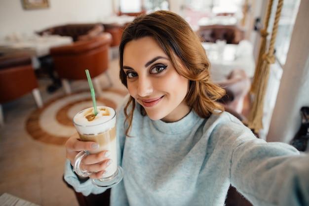 Hermosa chica haciendo autorretrato con café con leche en el café