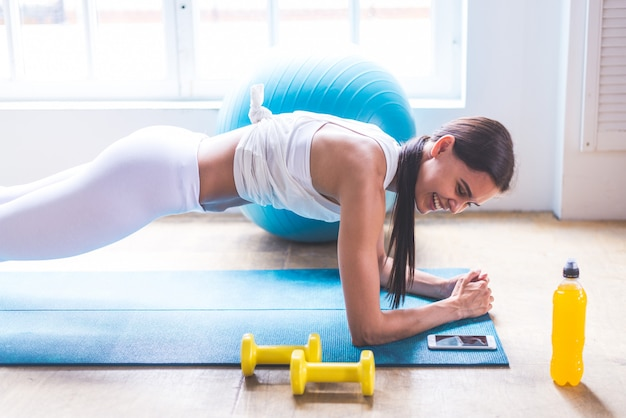 Hermosa chica haciendo entrenamiento y yoga en casa por la mañana
