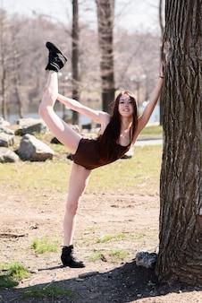 Hermosa chica haciendo estiramientos en la naturaleza.