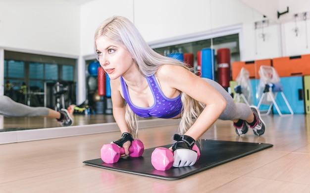 Hermosa chica haciendo flexiones en pesas