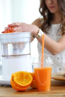 Hermosa chica haciendo jugo de naranja