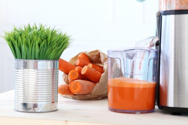 Hermosa chica haciendo jugo de zanahoria