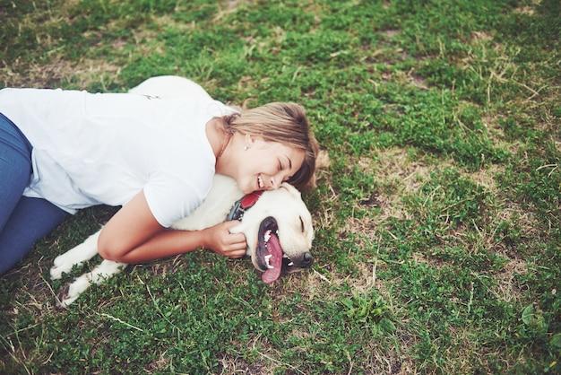 Hermosa chica con un hermoso perro en un parque sobre la hierba verde.