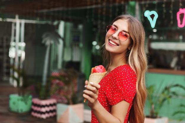 Hermosa chica hipster en gafas de sol comiendo helado y sonriendo