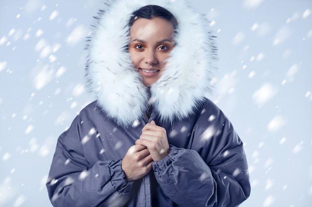Hermosa chica hispana encantadora en abrigo azul con nieve que cae