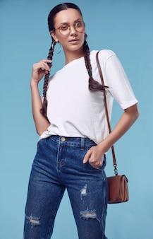 Hermosa chica hispana encantadora en camiseta blanca, jeans y gafas