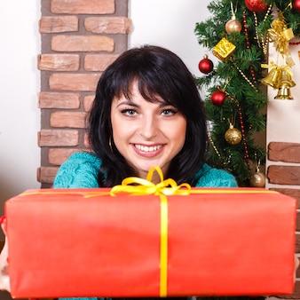 Hermosa chica en un interior de navidad da una caja de regalo roja
