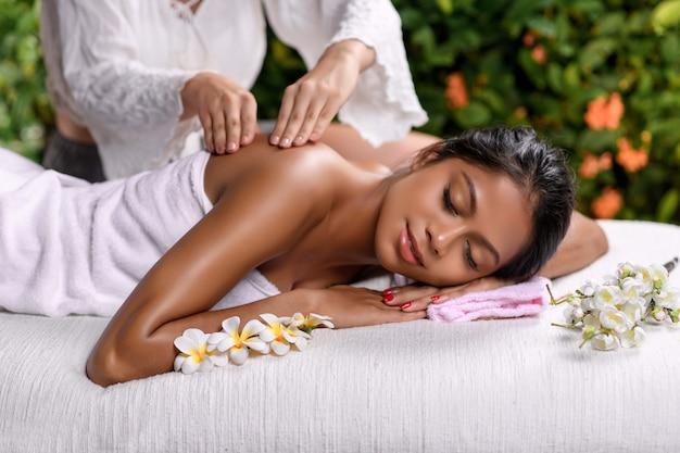 Hermosa chica interracial se acuesta de lado con los ojos cerrados en una mesa de masaje con ramitas de flores y recibe un masaje de espalda