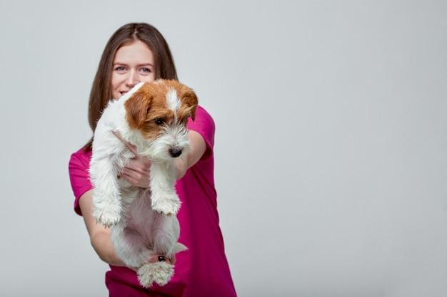 Hermosa chica con un jack russell terrier en sus manos sobre un fondo gris, espacio de copia