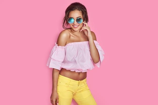 Hermosa chica en jeans amarillos y camisa rosa con las manos en alto con gafas de sol posando bailando sonriendo en espacio rosa en estudio