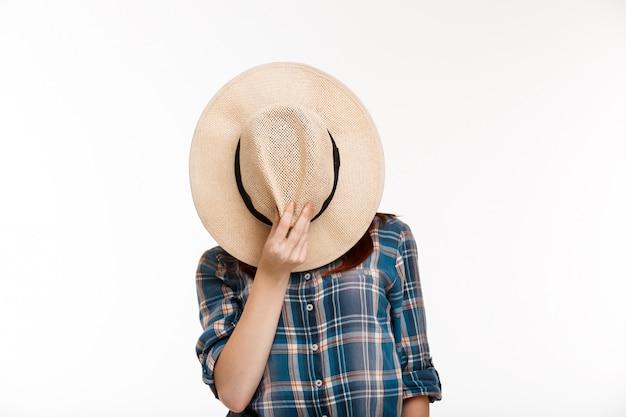 Hermosa chica jengibre escondiendo su rostro con sombrero sobre pared blanca.