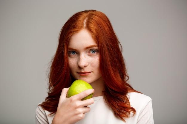 Hermosa chica de jengibre con manzana sobre pared gris.
