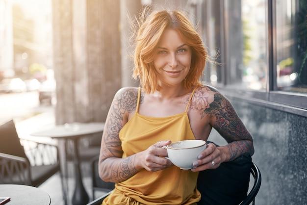 Hermosa chica jengibre tatuada en café
