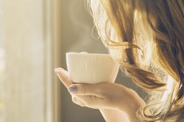 Hermosa chica joven bebe café solo en el café