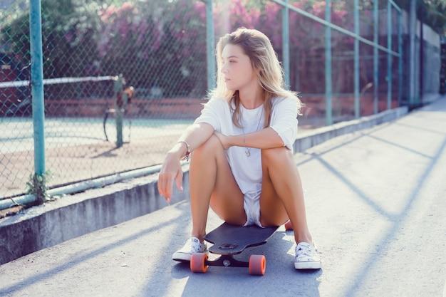 Hermosa chica joven sexy en pantalones cortos con longboard en tiempo soleado